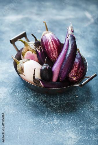 Colorful purple eggplants over linen napkin. Copy space.