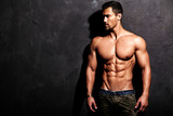 Portrait of strong healthy handsome Athletic Man Fitness Model posing near dark gray wall