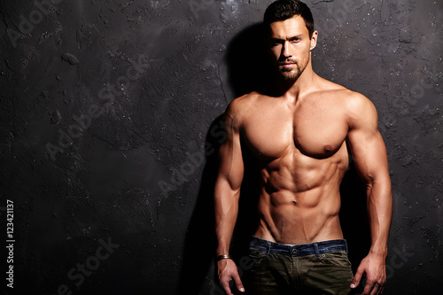 Portrait of strong healthy handsome Athletic Man Fitness Model posing near dark Tablou Canvas