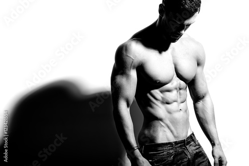 Portrait of strong healthy handsome Athletic Man Fitness Model posing near white Wallpaper Mural