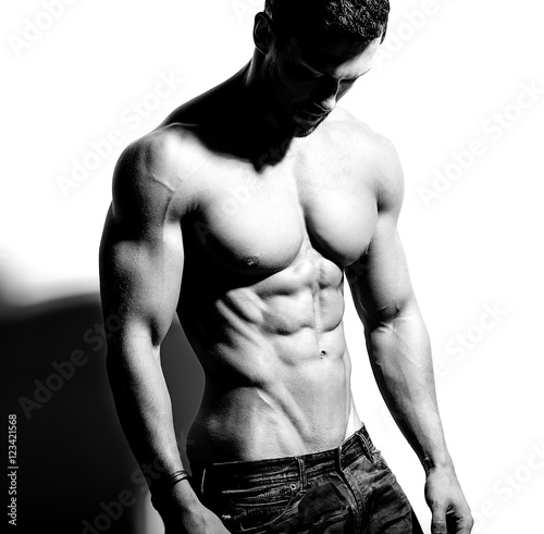 Portrait of strong healthy handsome Athletic Man Fitness Model posing near white Canvas Print