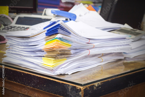 Fotografía  Pile of documents on desk stack up high waiting to be managed