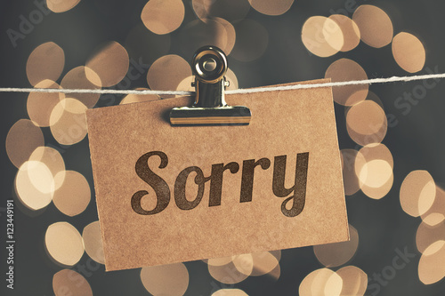Sorry sign pegged to a string with blurred bokeh lights in the background Wallpaper Mural