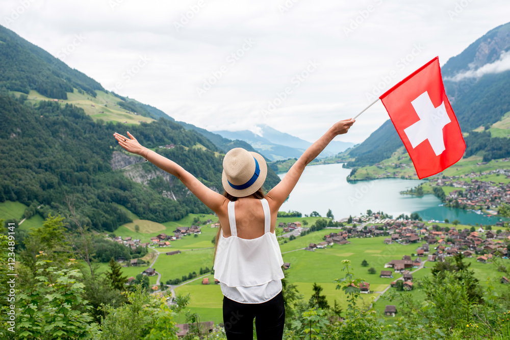 Fototapeta Young woman with swiss flag enjoying great landscape view on the valley with lake and village in Switzerland.