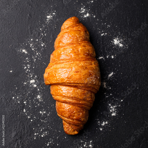 Cuadros en Lienzo Fresh croissant Black slate background. Top view