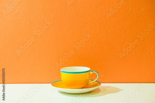 Fototapeta Yellow coffee cup with orange wall obraz na płótnie