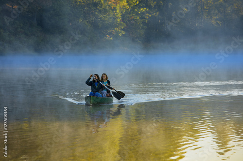 Fotografie, Obraz  Mother and daughter canoeing in morning mist, North Carolina