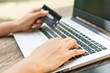 Woman Hands holding credit card and using laptop on wooden table