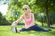 Starting training session outdoor.Full length shot of beautiful woman sitting in grass and stretching after morning run.