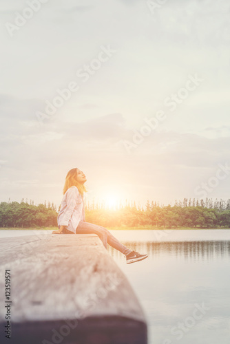 Photo  Young beautiful hipster woman sitting on the lake relaxing with