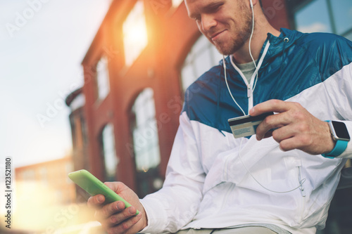 Fotografía  Man sitting outdoors with credit card and mobile phone, internet banking and onl