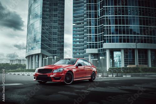 Obraz Red car stay on asphalt road in the city at daytime - fototapety do salonu