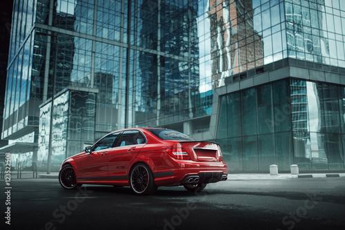 Zdjęcie XXL Czerwony samochód zostaje na asfaltowej drodze w mieście przy dziennym