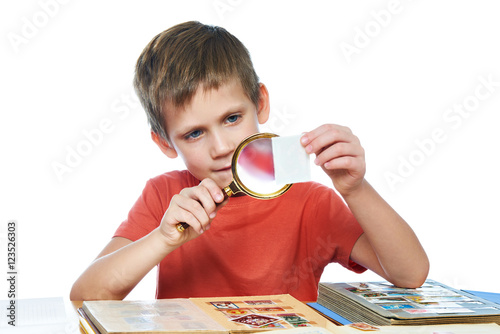 Cuadros en Lienzo  Boy with magnifier looks his stamp collection isolated