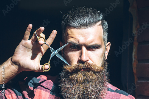 Foto  Man hipster with scissors