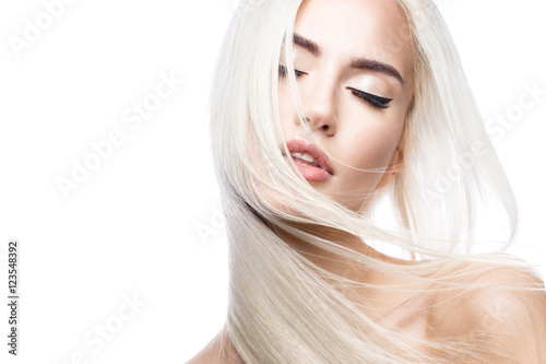 Fotografia Beautiful blond girl in move with a perfectly smooth hair, and classic make-up