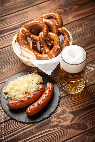 Pretzels, bratwurst and sauerkraut on wooden table Poster