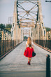 stylish portrait of a beautiful young woman on the bridge in a red skirt and black hat on a sunny day at sunset posing and smiling Life Style