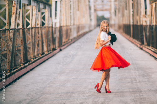Stampa su Tela stylish portrait of a beautiful young woman on the bridge in a red skirt and bla