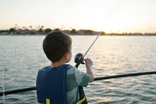 Papiers peints Peche Boy fishing in sea while standing on sailboat