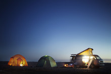 Camping Equipment At Beach Against Blue Sky At Night