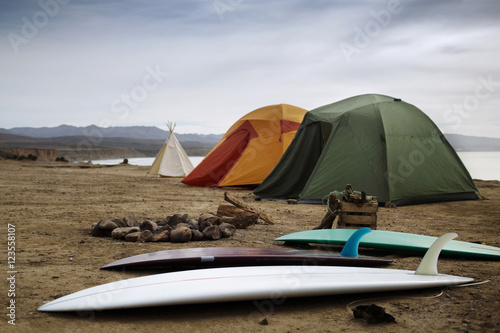 Camping equipment at beach against sky