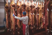 Butcher Putting A Tag On The Red Meat Hanging In Storage Room