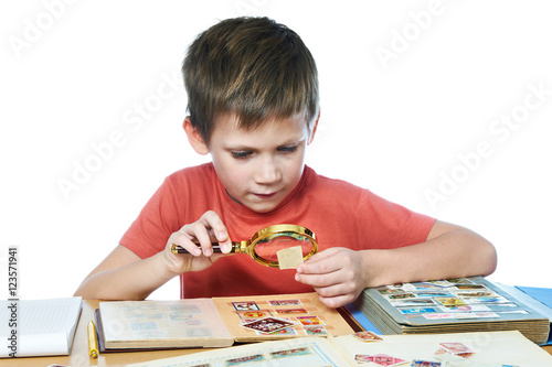 Fotografía Boy with magnifier looks his stamp collection isolated