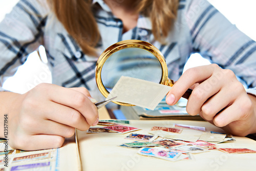 Cuadros en Lienzo Teen girl with magnifier looks his stamp collection isolated
