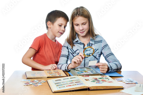 Fotomural Teen girl and little boy with magnifier looking his stamp collection isolated