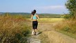 Tracking camera of woman girl with headphones running jogging in sunflower field