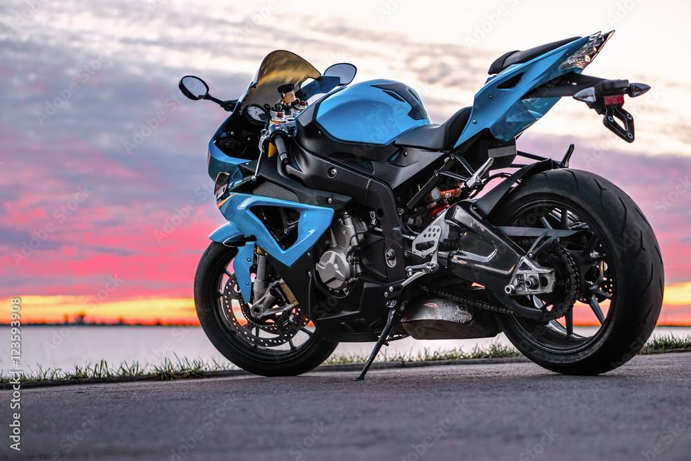 Trägt Motorrad auf dem Ufer bei Sonnenuntergang zur Schau Foto ...
