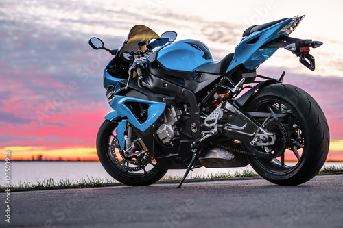 Photo  Sports motorcycle on the shore at sunset