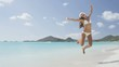 Christmas vacation travel woman jumping on beach of joy on white sand beach on winter holidays. Girl wearing santa hat arms raised of happiness during vacations travel. RED EPIC SLOW MOTION.