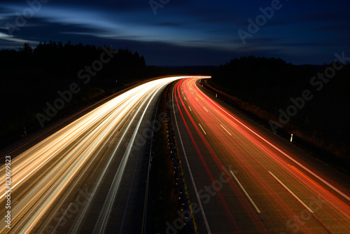 Fotobehang Nacht snelweg Winding Motorway at night, long exposure of headlights and taillights in blurred motion