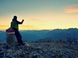 Hiker takes selfie photo. Man sit on Austria Germany border stone on Alpine mountain.