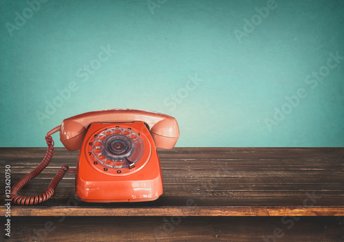 Old retro red telephone on table with vintage green pastel background Fototapete