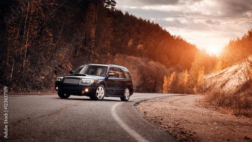 czarny-samochod-na-asfaltowej-drodze-przy-zmierzchem