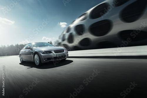 Zdjęcie XXL Jazdy samochodem na drodze asfaltowej w pobliżu nowoczesnego budynku w ciągu dnia