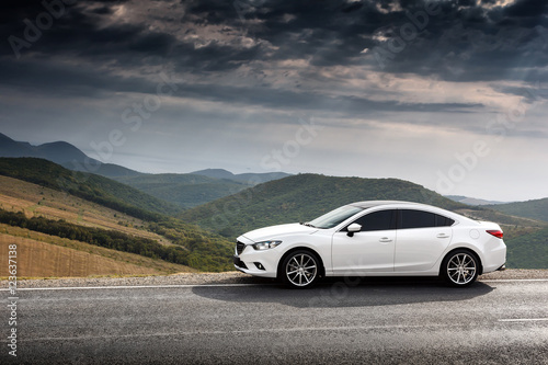 Foto  White Car parket at countryside asphalt road near green mountains at daytime