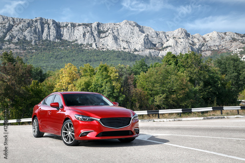 Zdjęcie XXL Czerwona samochodowa pozycja na drogowych pobliskich górach przy dniem