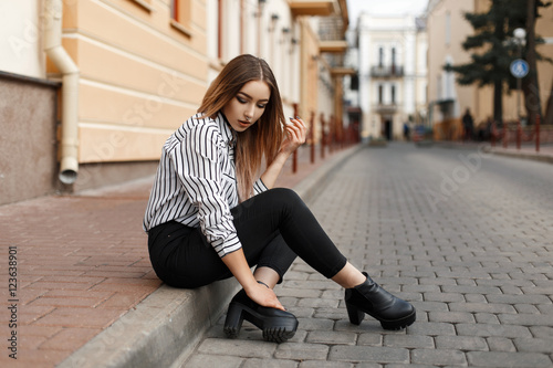 Beautiful stylish young woman in striped blouse sitting Wallpaper Mural