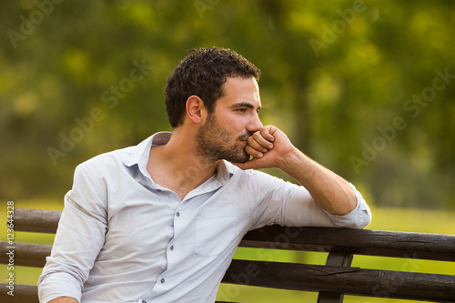 Fotografía  Worried businessman is sitting at the park and thinking about something