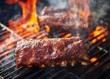 Grilling Barbecue Ribs On Flaming Grill