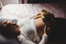 Pregnant Woman Holding Teddy B...