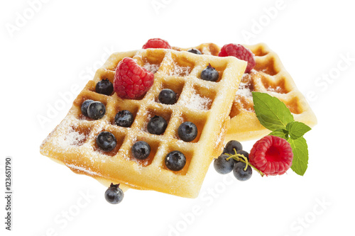 Homemade Belgian Waffles with raspberries and blueberries isolated on white background