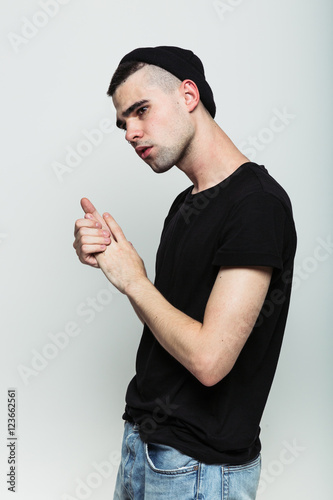 Fotografía  Studio shoot of worrying young man wearing black t-shirt jeans and hat rubbing hands