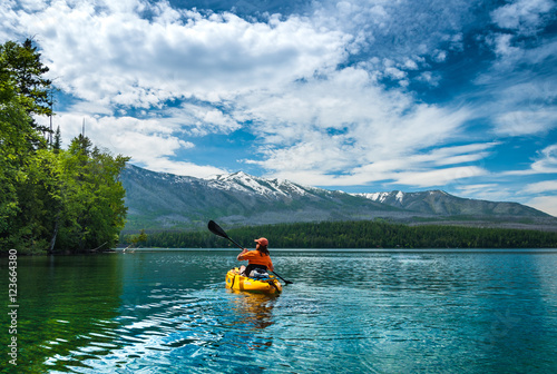 Valokuva  Kayaking in the spring by snow covered mountains on Lake McDonald in Glacier Nat