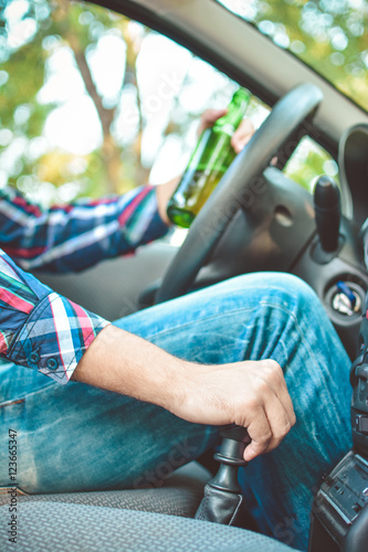 Drunk young man driving a car with a bottle of beer. Don't drink and drive concept. Driving under the influence. DUI, Driving while intoxicated