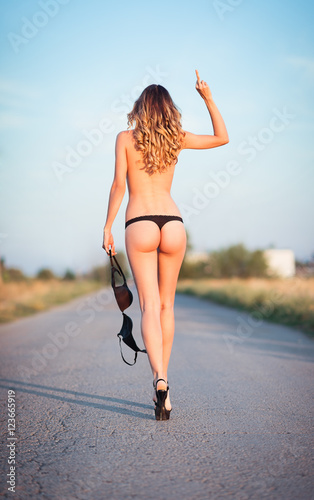 Sexy young woman going by the road and showing offensive gesture (middle finger) Wallpaper Mural